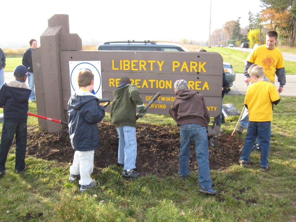 Area children lend a helping hand, planting flowers under the sign to Liberty Park.